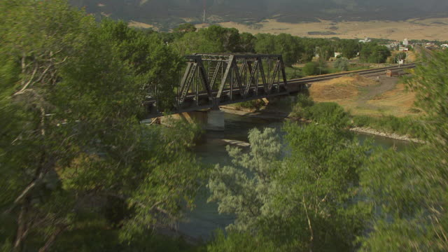 WS AERIAL TU View of grass to railroad bridge over Yellowstone River and town / Livingston, Montana, United States