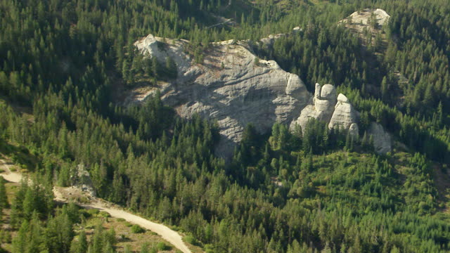 WS AERIAL ZI View of gray rock formation surrounded by trees Wenatchee National Forest / Washington, United States