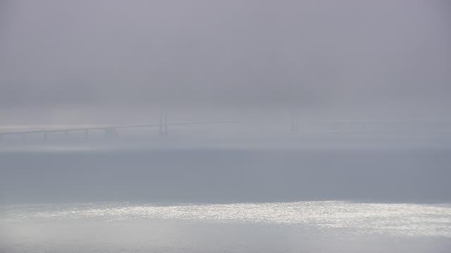 ws aerial zi view of great belt bridge through cloud / zealand, denmark - hd format stock-videos und b-roll-filmmaterial