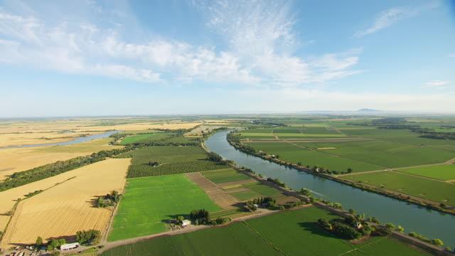 vídeos y material grabado en eventos de stock de ws aerial pov view of green farmland with river / california, united states - paisaje mosaico