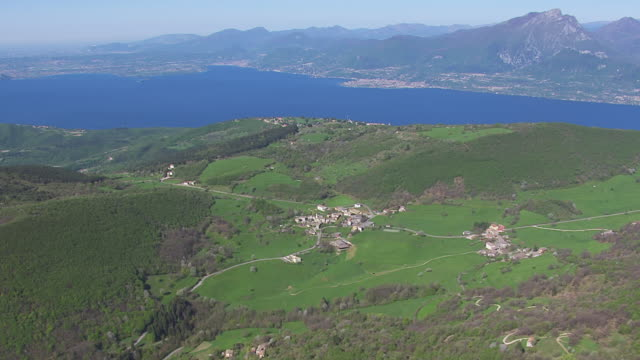 WS View of green field lake and mountain / Lake Garda, Trentino, Verona, Brescia