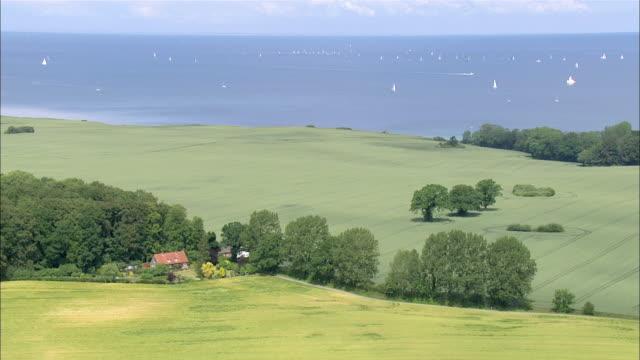 aerial ws view of green field near ocean / kiel, schleswig-holstein, germany - schleswig holstein stock-videos und b-roll-filmmaterial