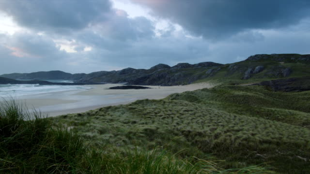WS PAN View of green meadows by beach with wind and clouds / Oldshoremore, Scotland, United Kingdom