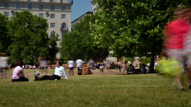 WS T/L View of Green Park London West End summer people relaxing on grass and deck chairs / London, Greater London, United Kingdom