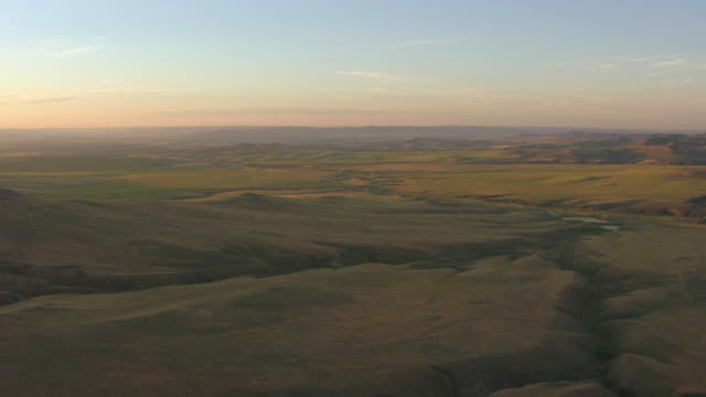 stockvideo's en b-roll-footage met ws aerial view of green river beds with hills in back side with morning sunshine in campbell county / wyoming, united states - vlakte