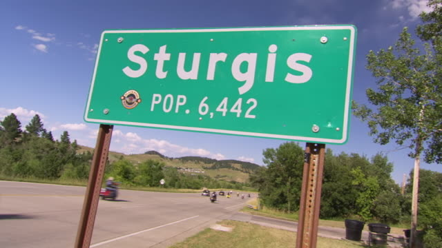 WS View of Green sign saying STURGIS POP 6442 with motor cyclists passing by on highway / Sturgis, South Dakota, United States