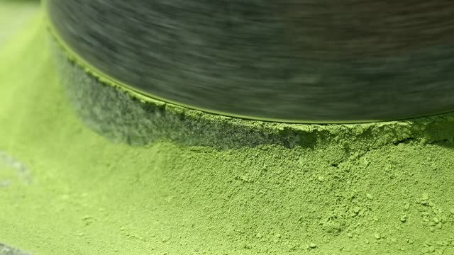 view of green tea powder coming out from millstone - millstone stock videos & royalty-free footage