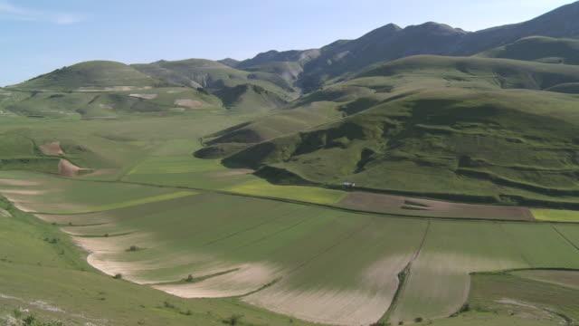 ws view of green valley meadow and mountain range / castelluccio di norcia, umbria, italie - ウンブリア州点の映像素材/bロール