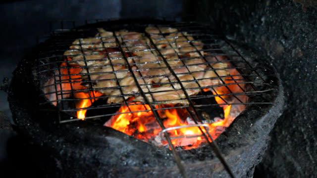 vidéos et rushes de view of grilling the meats on a charcoal fire - fondu d'ouverture