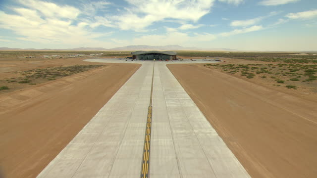 ws aerial tu view of ground to runway to reveal spaceport america / new mexico, united states - 飛行機格納庫点の映像素材/bロール