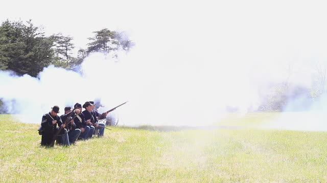 vídeos de stock e filmes b-roll de ws view of group of union soldiers fire their rifles and canon as smoke blowing over / appomattox, virginia, united states - exército da união