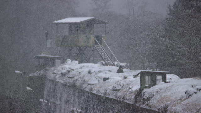 vidéos et rushes de view of guard post in snowy day near dmz (demilitarized zone, a strip of land running across the korean peninsula), south korea - frontière