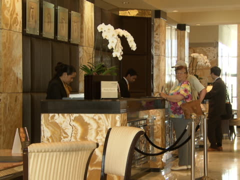 view of guests standing at the reception desk of the intercontinental hotel - intercontinental hotels group stock videos & royalty-free footage