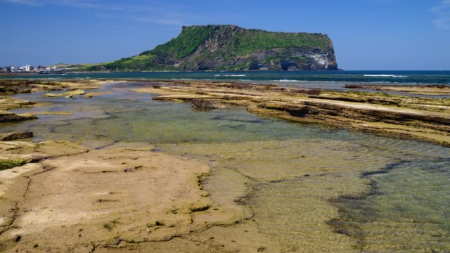 view of gwangchigi beach and seongsan ilchulbong tuff cone in seogwipo, jeju island - felswand stock-videos und b-roll-filmmaterial