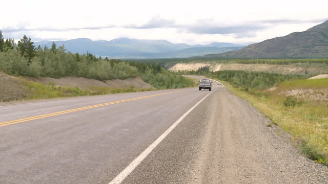 vidéos et rushes de ws view of haines highway, several cars and pickups passing in both directions, mountains and hills in back side near kluane national park and reserve / yukon, canada - canada