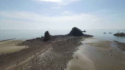 view of halmibawi rock (famous travel destination for watching sunset) at low tide in anmyeondo island, south korea - 干潮点の映像素材/bロール