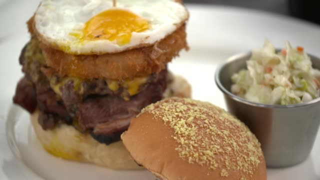 view of hamburger being placed on plate with coleslaw - coleslaw stock videos & royalty-free footage
