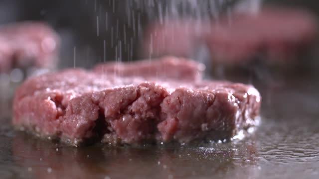 view of hamburger patty being seasoned with salt on griddle - zutaten stock-videos und b-roll-filmmaterial