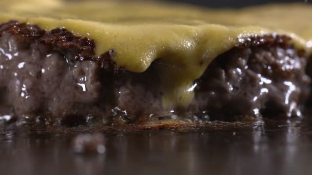 view of hamburger patty with cheese being grilled on griddle - speisen und getränke stock-videos und b-roll-filmmaterial