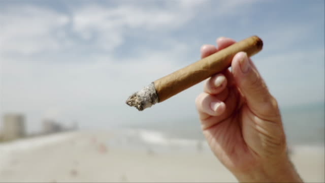 CU SLO MO View of hand holding cigar and flicking ashes / Jacksonville Beach, Florida, USA