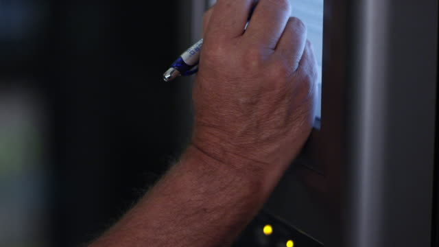 view of hand holding stylus tapping monitor - netzwerkadministrator stock-videos und b-roll-filmmaterial