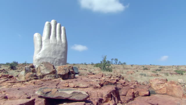 WS T/L View of Hand statue on hill area, clouds pass overhead / North West Province, South Africa