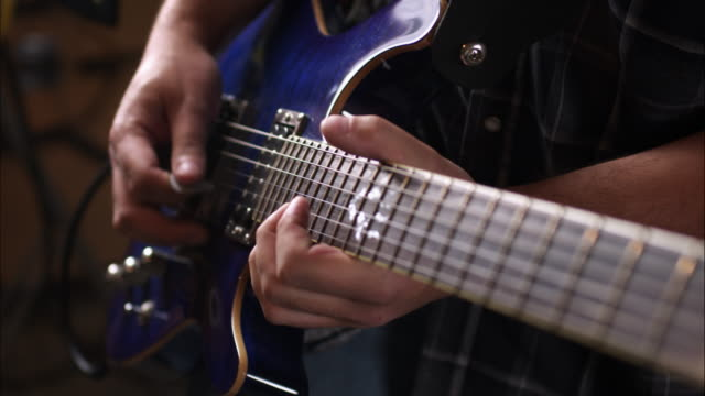 View of hands playing electric guitar.