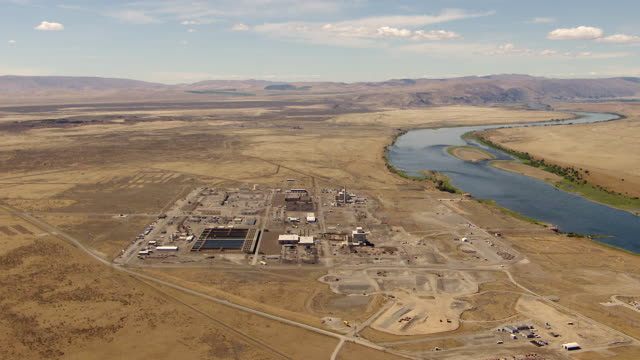 ws aerial view of hanford site nuclear production complex on columbia river with surrounded by empty hills / richland, washington, united states - hanford nuclear reservation video stock e b–roll