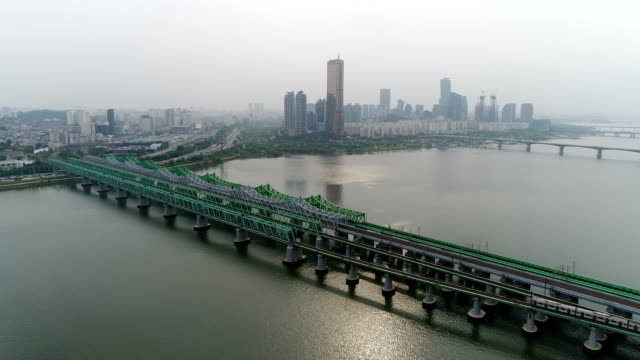 vidéos et rushes de view of hangangcheolgyo (railroad bridge) running over han river and 63 building (the tallest building 1990s in korea) in yeouido district, seoul at day - train de banlieue
