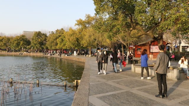 vídeos de stock, filmes e b-roll de view of hangzhou west lake tourist area people gathering around west lake on a sunny weekend after staying at home for days chinese authorities... - símbolo de resíduos biológicos