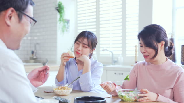 view of happy family eating breakfast with conversation - korean ethnicity stock videos & royalty-free footage