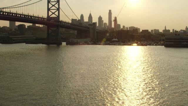 ms aerial view of harbor with benjamin franklin bridge and skyscrapers in city / philadelphia - ベンフランクリン橋点の映像素材/bロール