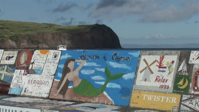 vídeos de stock, filmes e b-roll de ws view of harbour wall with painting, ship passing behind / horta harbour, faial island, azores, portugal - muro