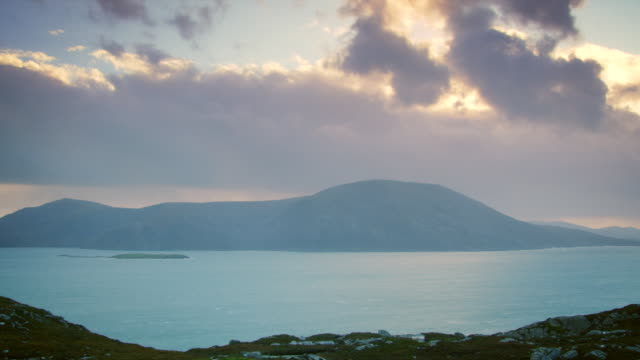 ws t/l pan view of harris island hills by see with evening light and clouds / harris island, scotland, united kingdom - 2k resolution stock videos and b-roll footage