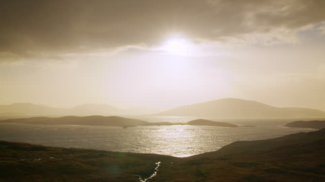 ws pan view of harris island hills by see with evening light and clouds / harris island, scotland, united kingdom - 2k resolution stock videos and b-roll footage