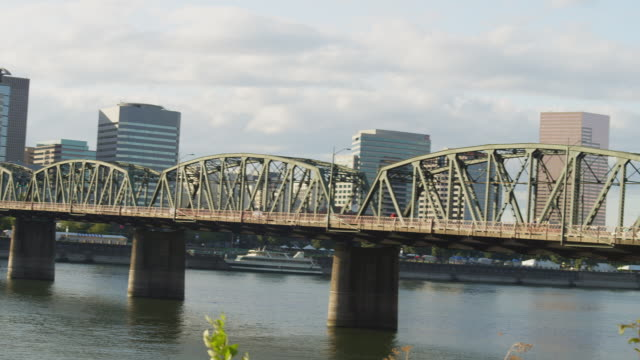WS PAN View of Hawthorne bridge leading to Portland Oregon city center at sunset and Willamette river in front side / Portland, Oregon, United States