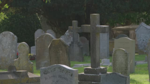 view of headstones in a churchyard in sunshine - 宗教上のシンボル点の映像素材/bロール