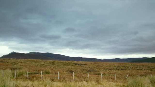 WS T/L View of heathland meadows closed by fence and hills with clouds / Crask Inn, Scotland, United Kingdom