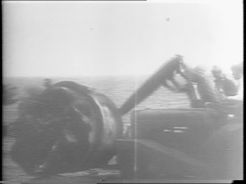 view of heavily damaged navy carrier, the uss bunker hill / huge hole in the deck / pilots and sailors survey damage on deck / smoke emits from... - 船体点の映像素材/bロール