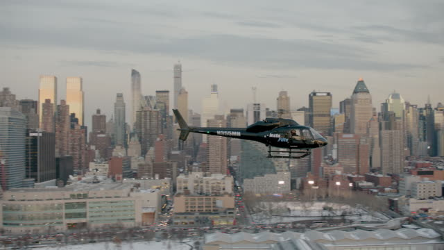 AERIAL MS TS View of helicopter flying over city with tall buildings on distance / New York City