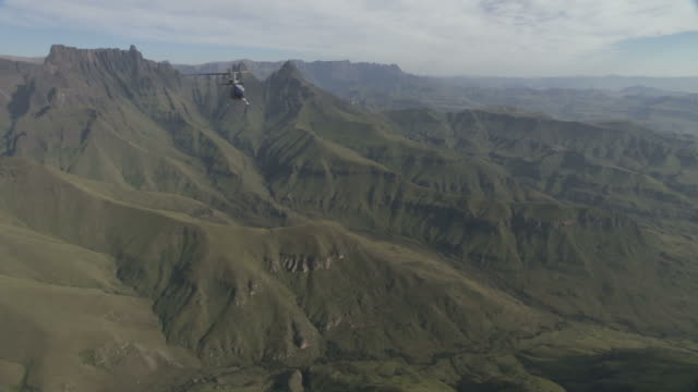 ws aerial ts view of helicopter flying over grassy mountain range / kwazulu natal, south africa - drakensberg mountain range stock videos & royalty-free footage