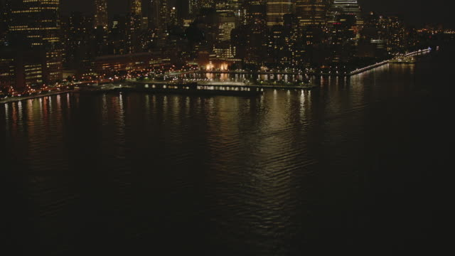 MS TS ZI AERIAL View of helicopter flying over hudson river near harbor at night / New York City