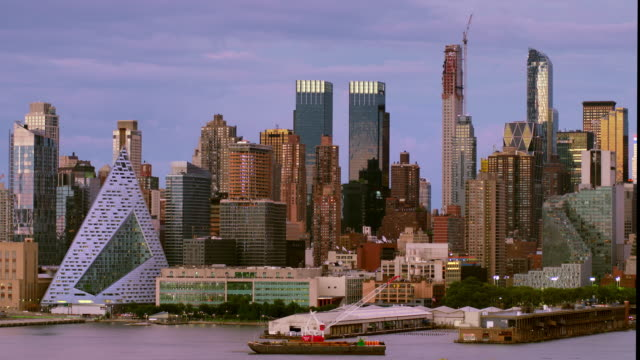 view of hell's kitchen in manhattan from across the hudson river on a clear evening. - hell's kitchen stock videos and b-roll footage