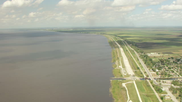 WS AERIAL View of Herbert Hoover Dike and lake and surrounding landscape / Lake Okeechobee, Florida, United States