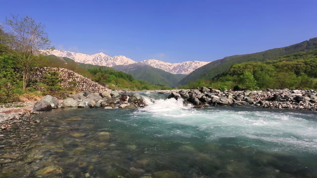 ws view of hida mountains, northern alps and melted snow river / hakuba, nagano prefecture, japan  - 川点の映像素材/bロール
