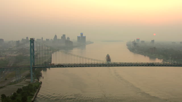 ws aerial view of high flyover detroit river with ambassador bridge at sunrise / detroit, michigan, united states - detroit river stock-videos und b-roll-filmmaterial