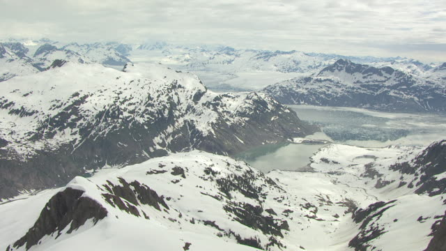 ws aerial view of high over snowy mountains looking over columbia glacier / alaska, united states - columbia glacier stock videos & royalty-free footage