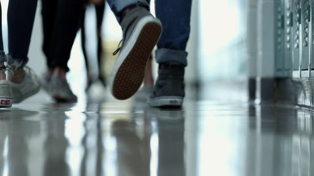 vídeos de stock, filmes e b-roll de view of high school students feet and legs walking in hallway - colégio educação