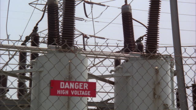 ms pan view of high voltage sign on fence of electric power plant - high voltage stock videos & royalty-free footage