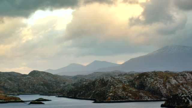 ws t/l pan view of highlands scenery by ocean and snowy capped mountains with evening light and clouds / kinlochbervie, scotland, united kingdom - scottish highlands stock videos & royalty-free footage
